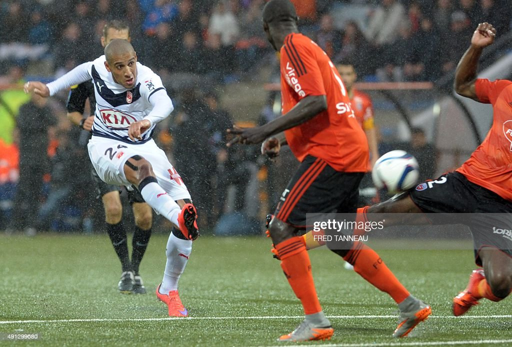 Bordeaux's Tunisian midfielder Wahbi Khazri (L) shoots the ball which is deflected by Lorient's defender Lamine Kone (R) during the French L1 football match between Lorient and Bordeaux at Moustoir Stadium in Lorient, western France, on October 4, 2015. Lorient won the match 3-2.