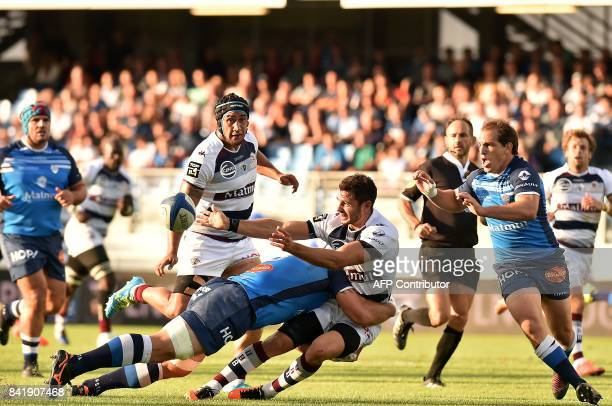 Bordeaux's winger Nans Ducuing passes the ball as he is tackled during the French Top 14 Rugby Union 14 Castres vs Bordeaux Begles on September 2...