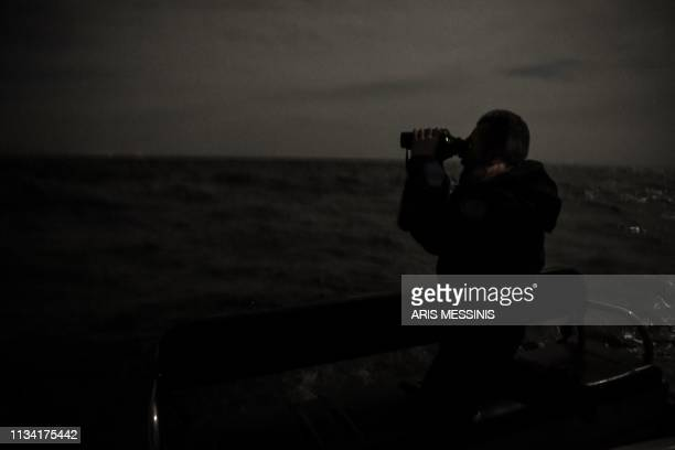 EU border agency FRONTEX member from Portugal looks though his night vision binoculars as he patrols on a boat with collegues to examine the area...