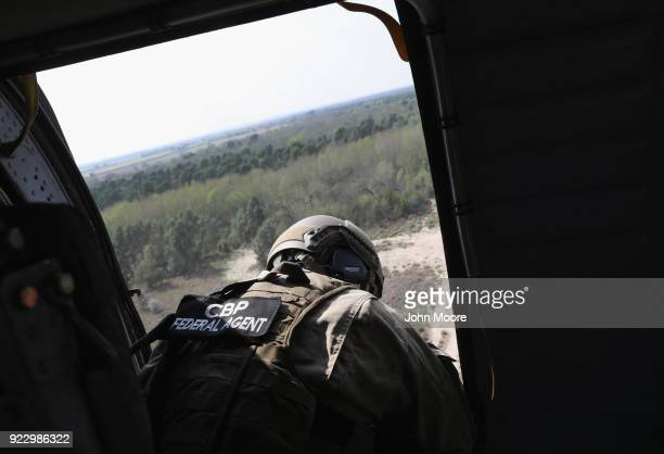 S border agent scans thick brushland near the USMexico border from a Black Hawk helicopter on February 21 2018 near McAllen Texas Customs and Border...