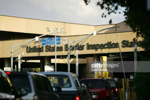 A border agent walks on roof of the US border inspection station as cars pass wait in typically long lines to enter the United States from Mexico on...