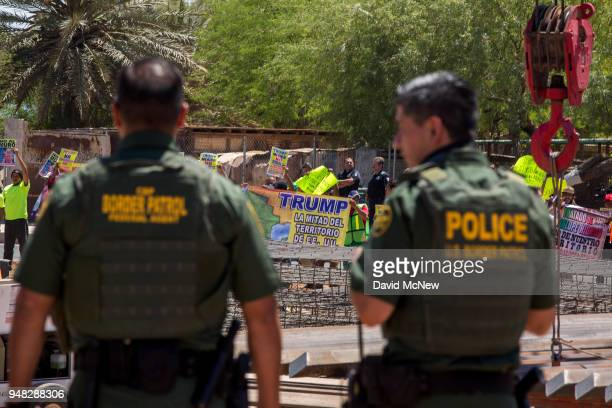 Border agents watch as protesters on the Mexico side of the border demonstrate against policies of President Donald Trump while US Department of...