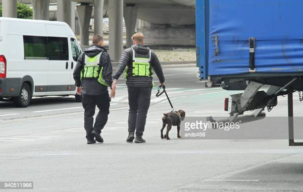 Border control at Dover port UK, two security guards and a trained sniffer dog
