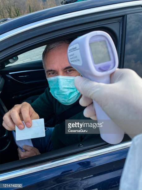 border control with body temperature measurement during covid-19 crisis - infrared thermometer stock pictures, royalty-free photos & images