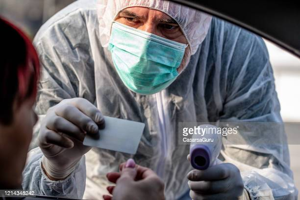 covid-19 – border controls using paramedics to check driver's health conditions - driving mask stock pictures, royalty-free photos & images