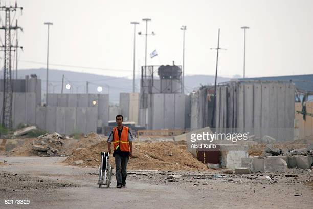 Border crossing worker pushes a wheel chair as he returns to the Palestinian side of the Erez Crossing afteer helping a patient to cross the border...