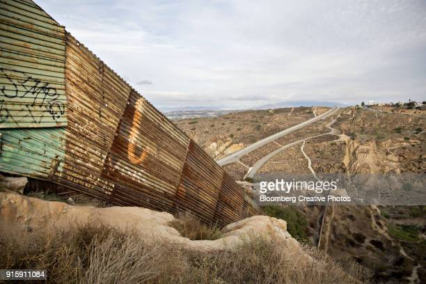 a border fence stands along the u.s.-mexico border - mexico border wall stock pictures, royalty-free photos & images