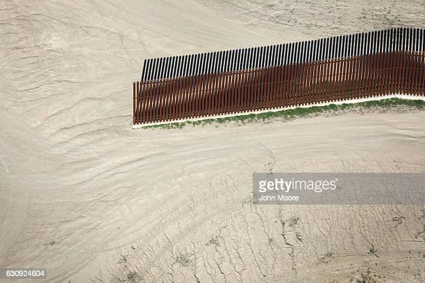 A border fence stops near the USMexico border formed by the Rio Grande on January 3 2017 near McAllen Texas Thousands of undocumented immigrants are...