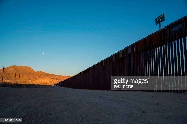 Border fencing is pictured on the USMexican border in Anapra New Mexico under a full moon on March 19 2019 Speaking of an 'invasion' of illegal...