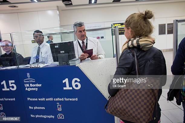 Border Force check the passports of passengers arriving at Gatwick Airport on May 28 2014 in London England Border Force is the law enforcement...