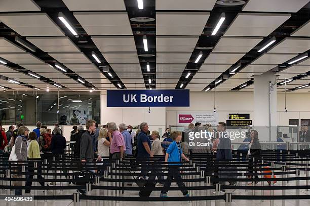 Border Force check the passports of passengers arriving at Gatwick Airport on May 28, 2014 in London, England. Border Force is the law enforcement...