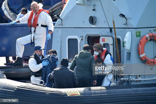 UK Border Force officers help migrants with children believed to have been picked up from boats in the Channel disembark from Coastal patrol vessel...