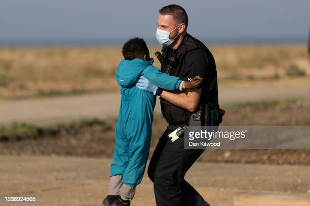 Border force official carries a migrant child after arriving via the RNLI on Dungeness beach on September 7, 2021 in Dungeness, England. The week has...