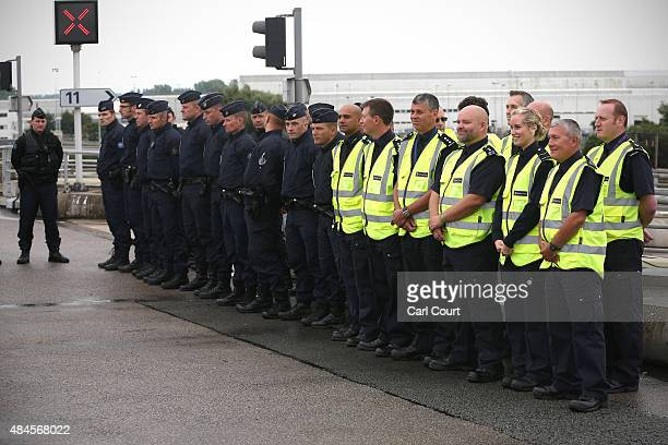 Border Force officials and French police officers line up ahead of a visit by Britain's Home Secretary Theresa May and French Interior Minister...