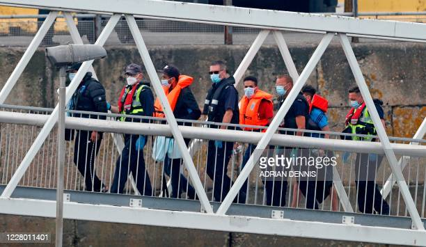UK Border Force officials escort migrants intercepted whilst travelling in a RIB from France to Dover as they walk up onto the quayside from the...