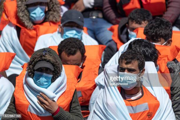 Border Force officials guide newly arrived migrants to a holding facility after being picked up in a dinghy in the English Channel on June 09, 2021...