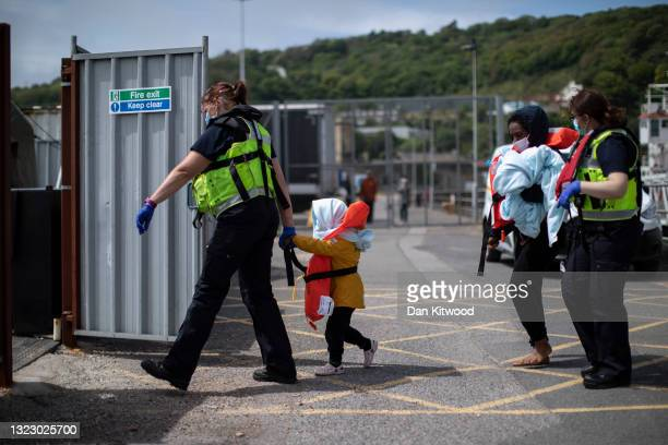 Border Force officials guide newly arrived migrants to a holding facility after being picked up in a dinghy in the English Channel on June 11, 2021...