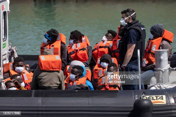 Border Force officials guide newly arrived migrants to a holding facility after being picked up in a dinghy in the English Channel on June 24, 2021...
