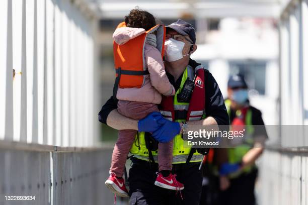 Border Force officials hold a young girl that arrived with other migrants after being picked up in a dinghy in the English Channel on June 09, 2021...