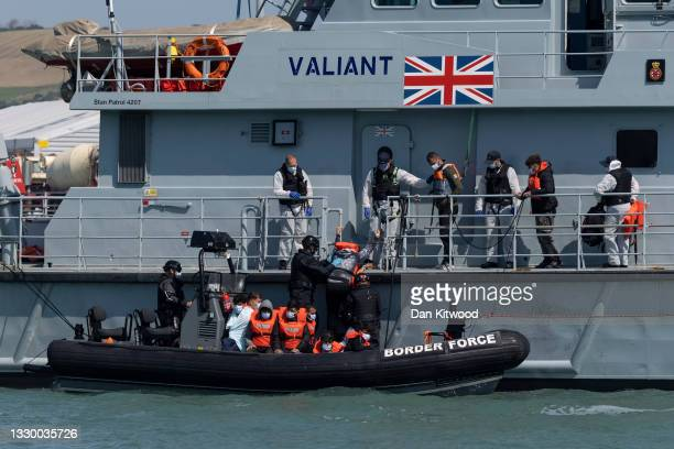 Border Force officials move newly arrived migrants between vessels outside of Dover Harbour on July 22, 2021 in Dover, England. On Monday, 430...