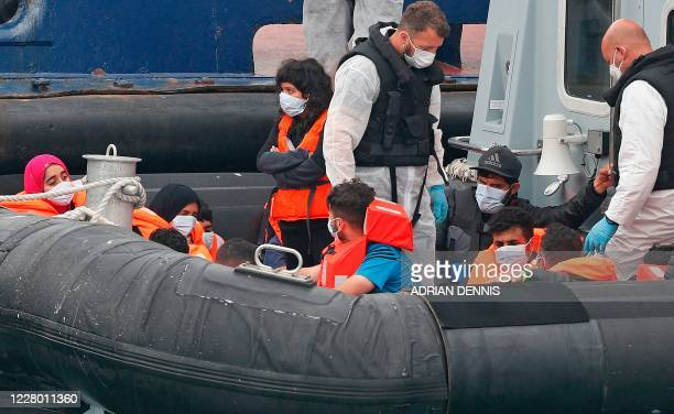 UK Border Force officials stand aboard their patrol vessel HMC Eagle with migrants intercepted whilst travelling in a RIB from France to Dover as...