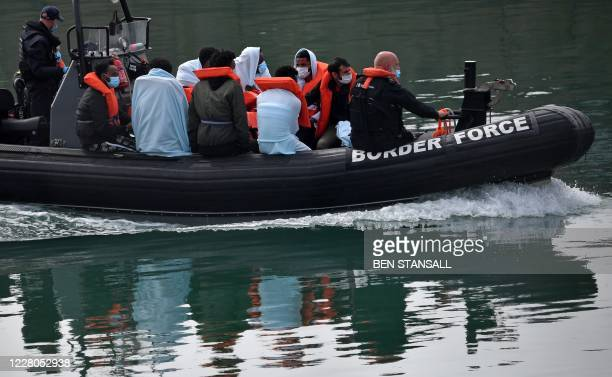 Border Force officials travel in a RIB with migrants picked up at sea whilst Crossing the English Channel, as they arrive at the Marina in Dover,...