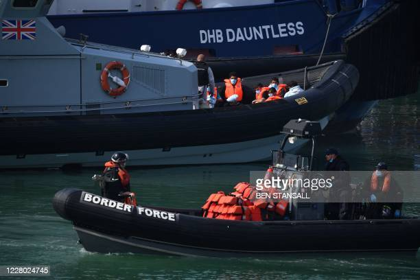 Border Force Patrol Vessel passes in the foreground as migrants intercepted whilst travelling in a RIB from France to Dover sit on the deck of the...
