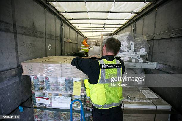 Border Force staff check inside the back of a lorry as it arrives at the UK border after leaving a crosschannel ferry on August 13 2014 in Portsmouth...