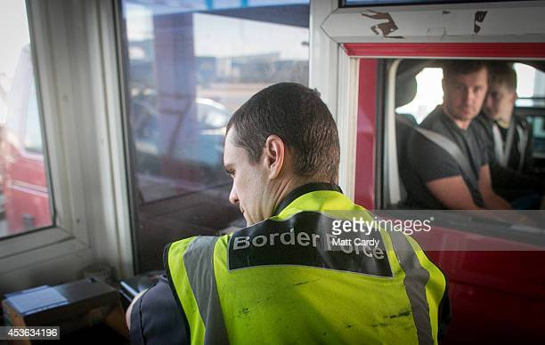 Border Force staff check passports of motorists arriving at the UK border after leaving a crosschannel ferry on August 13 2014 in Portsmouth England...
