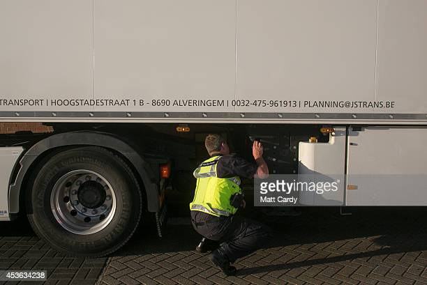 Border Force staff check underneath a lorry that has arrived at the UK border after leaving a crosschannel ferry on August 13 2014 in Portsmouth...