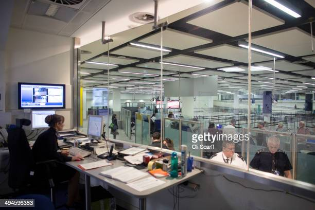 Border Force staff monitor the checking of passports of passengers arriving at Gatwick Airport from their control room on May 28 2014 in London...