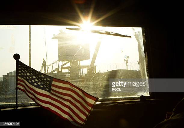 A border guard stands on Iraq's border with Kuwait behind a US flag fluttering on the dashboard of a Mine Resistant Ambush Protected vehicle from the...