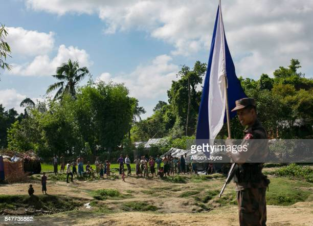A border guards holds a flag signaling that they want a meeting with Myanmar border guards looking into no man's land where Rohingya have set up...