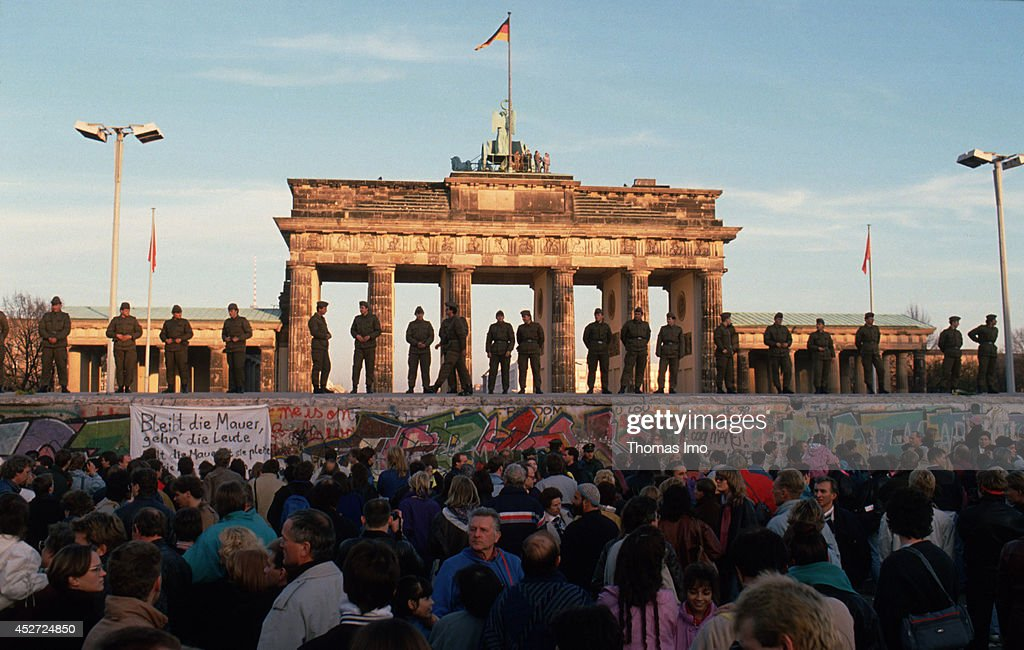 Border guards of the German Democratic Republic standing on the Berlin Wall observing demonstrating people on November 09, 1989, in Berlin, Germany. The year 2014 marks the 25th anniversary of the fall of the Berlin Wall.