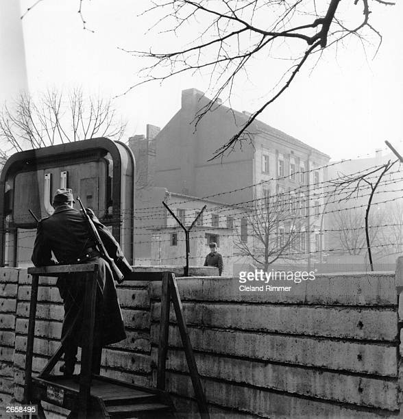 Border guards on opposite sides of the Berlin Wall viewed from western side