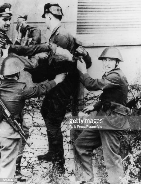 GDR border guards remove the body of Peter Fechter after he was shot trying to cross the Berlin Wall to West Germany 18th August 1962