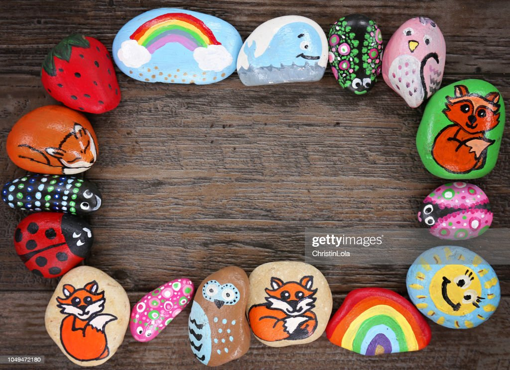 Border of Colorful Cartoon Hand Painted Animal Rocks on Wood Background : Stock Photo
