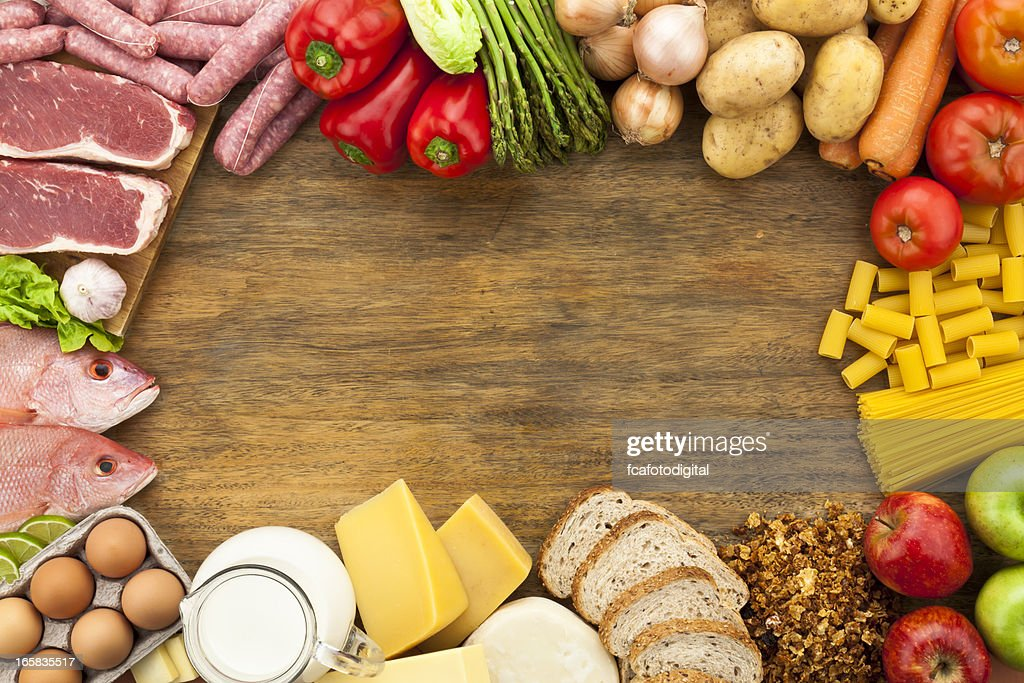 Border of different types of food on wooden table : Stock Photo