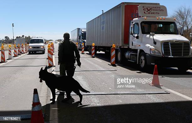 Border Patrol agent and drug sniffing German Shepherd Jack-D prepare to search vehicles for drugs at a checkpoint near the U.S. Mexico border on...