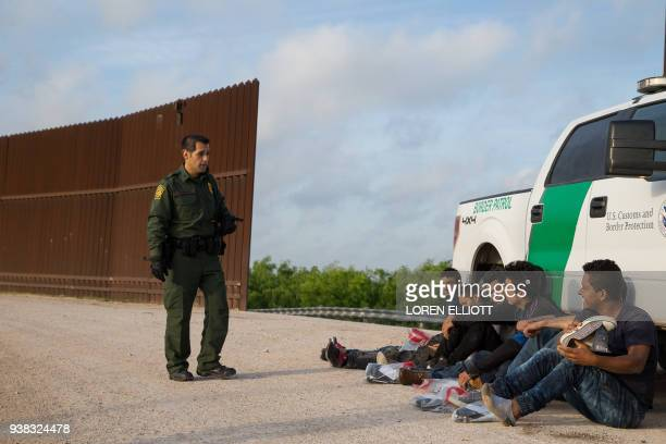 Border Patrol agent apprehends illegal immigrants shortly after they crossed the border from Mexico into the United States on Monday March 26 2018 in...