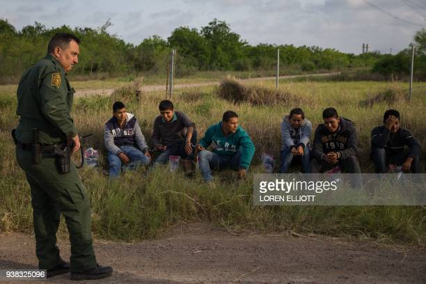 A Border Patrol agent apprehends illegal immigrants shortly after they crossed the border from Mexico into the United States on Monday March 26 2018...