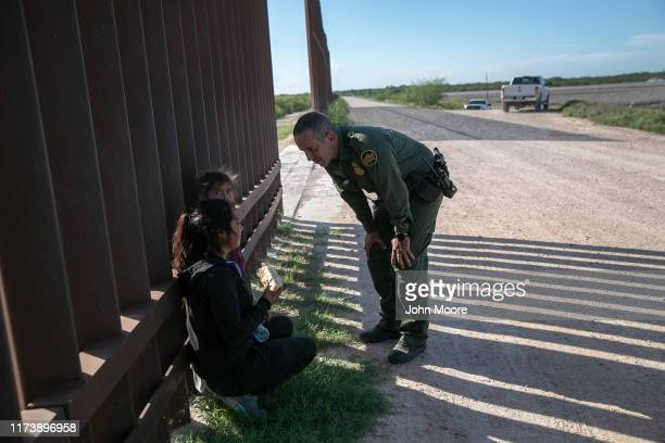 Border Patrol agent Carlos Ruiz speaks with a mother and daughter from Ecuador after apprehending them and giving them a sandwich on September 10,...