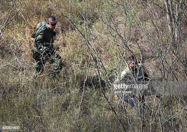 S Border Patrol agent chases an undocumented immigrant in thick brush near the USMexico border on January 3 2017 near Mission Texas Thousands of...