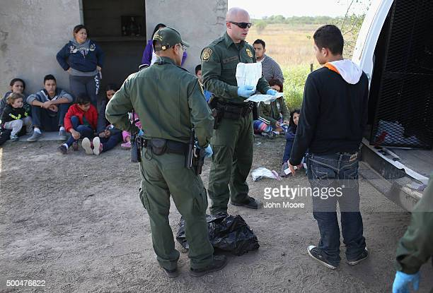 S Border Patrol agent checks a Central American migrant's documents on December 8 2015 near Rio Grande City Texas A group of immigrants had just...