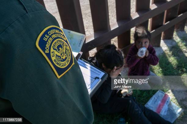 Border Patrol agent checks the passports of a mother and daughter from Ecuador next to the border fence, after detaining them on September 10, 2019...