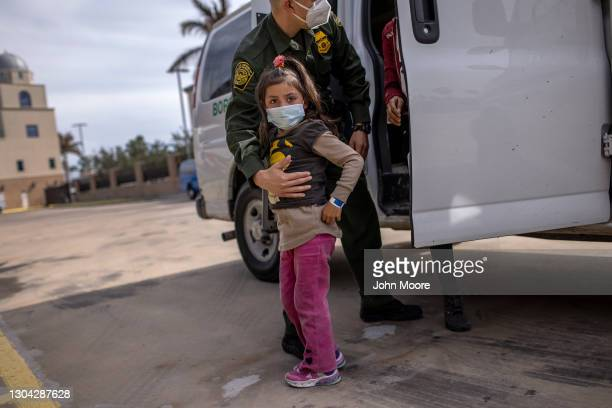 Border Patrol agent delivers a young asylum seeker and her family to a bus station on February 26, 2021 in Brownsville, Texas. U.S. Immigration...