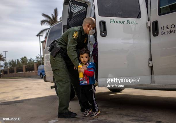 Border Patrol agent delivers a young asylum seeker and his family to a bus station on February 26, 2021 in Brownsville, Texas. U.S. Immigration...