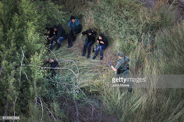 S Border Patrol agent detains a group of undocumented immigrants on October 18 2016 near McAllen Texas Border Patrol agents coordinate with US Air...