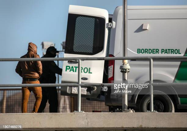 Border Patrol agent detains an immigrant who had crossed the U.S.-Mexico border on March 16, 2021 near Ciudad Juarez, Mexico. A surge of some 10,000...