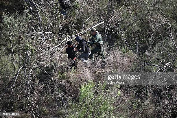 Border Patrol agent detains juvenile undocumented immigrants after capturing them in thick brush near the U.S.-Mexico border on December 10, 2015 at...